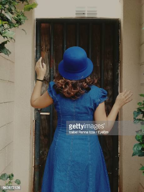 Rear View Of Young Woman Standing Against Door