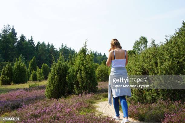 Rear View Of Young Woman Standing Against Plants