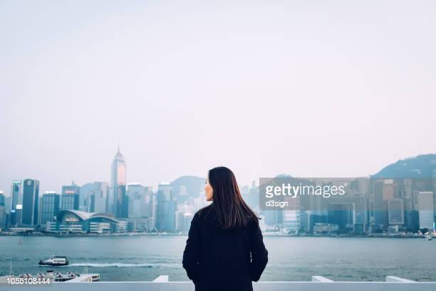 rear view of young woman standing against the promenade of victoria harbour overlooking the cityscape of hong kong - local landmark stock pictures, royalty-free photos & images