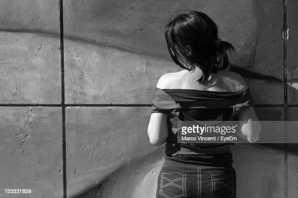 rear view of young woman standing against wall - one young woman only stock pictures, royalty-free photos & images