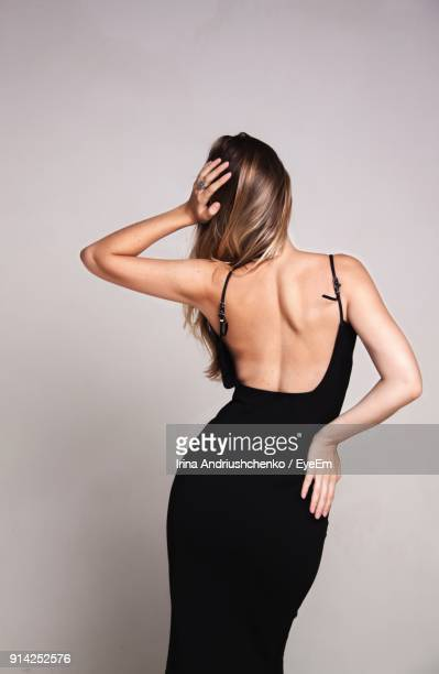 rear view of young woman standing against white background - long dress stock pictures, royalty-free photos & images