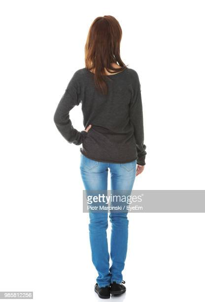rear view of young woman standing against white background - stare in piedi foto e immagini stock