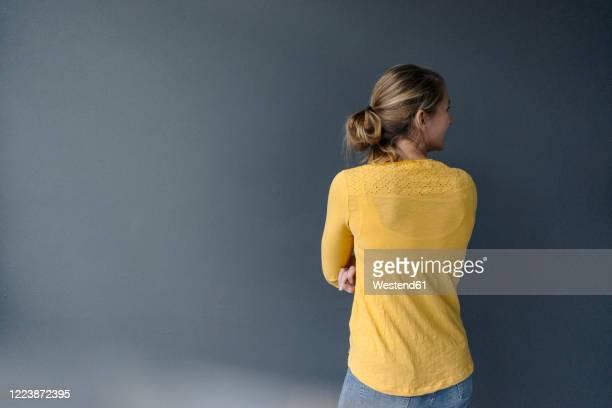 rear view of young woman standing at a grey wall - rückansicht stock-fotos und bilder