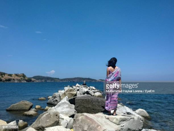 Rear View Of Young Woman Standing At Beach Against Clear Blue Sky