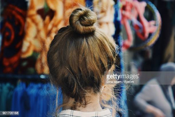 rear view of young woman standing at market - おだんごヘア ストックフォトと画像