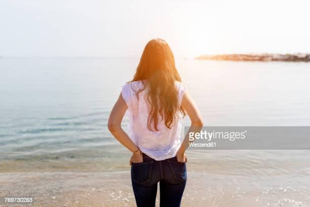 rear view of young woman standing at the sea - espalda chica morena playa fotografías e imágenes de stock