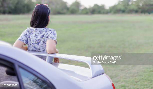 Rear View Of Young Woman Standing By Car At Park