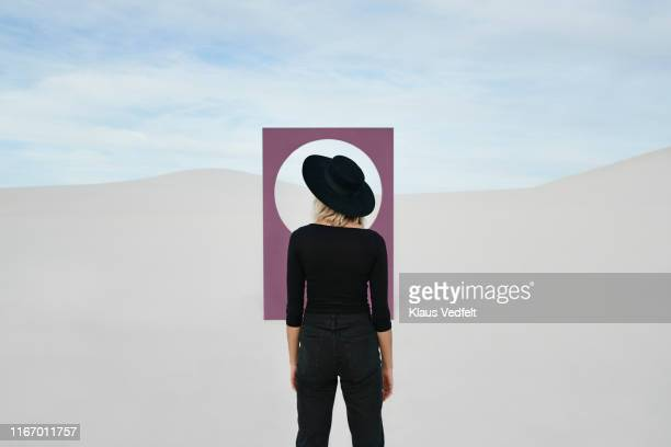 rear view of young woman standing by portal at desert against sky - 接近する 女性 ストックフォトと画像