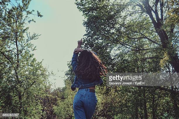 Rear View Of Young Woman Standing By Trees In Forest