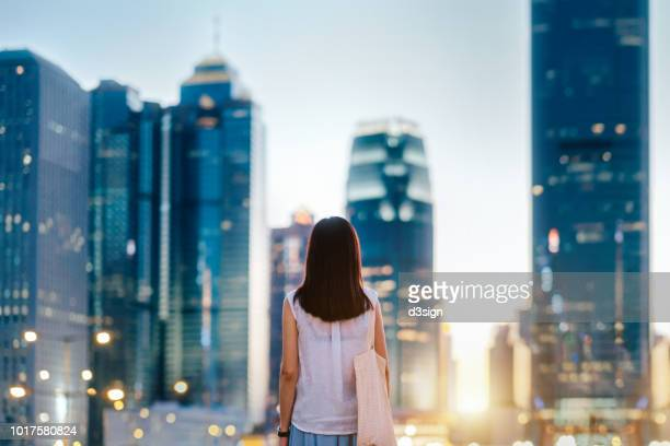 rear view of young woman standing in front of illuminated city skyline of hong kong at dusk - front view photos et images de collection