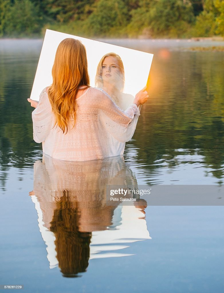 Rear view of young woman standing in lake holding mirror looking at reflection, lens flare : Stock Photo