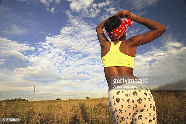 Rear view of young woman standing in remote field