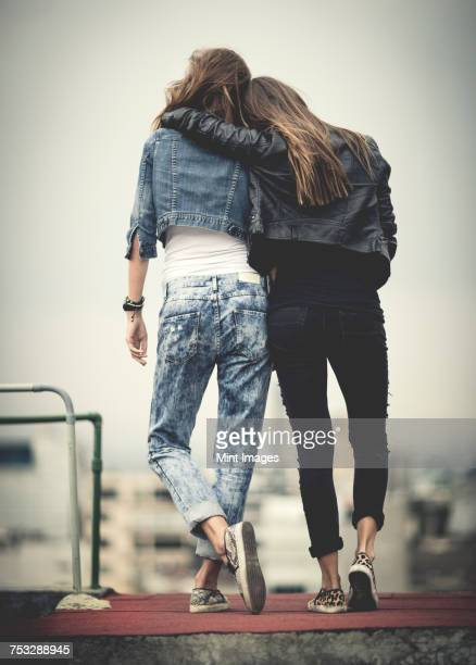 Rear view of young woman standing on a rooftop with their arms around each other.