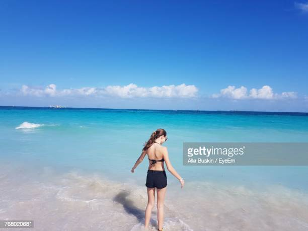Rear View Of Young Woman Standing On Beach