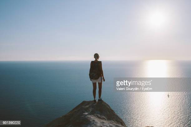 Rear View Of Young Woman Standing On Cliff By Sea Against Clear Sky