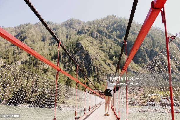 Rear View Of Young Woman Standing On Footbridge Leading Towards Mountain