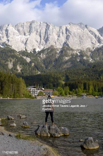 rear view of young woman standing on rocks in lake against mountains - lagarde stock pictures, royalty-free photos & images