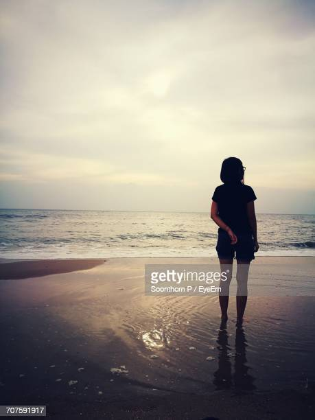 Rear View Of Young Woman Standing On Sea Shore Against Cloudy Sky During Sunset
