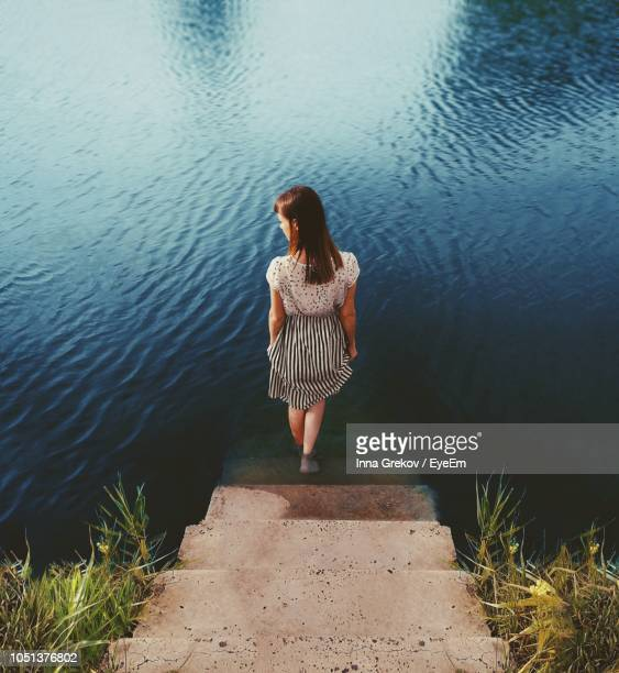 Rear View Of Young Woman Standing On Steps By Lake