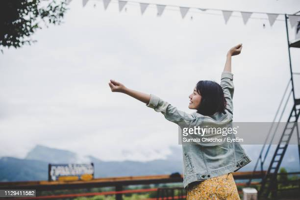 rear view of young woman stretching arms while standing against sky - 腕を上げる ストックフォトと画像