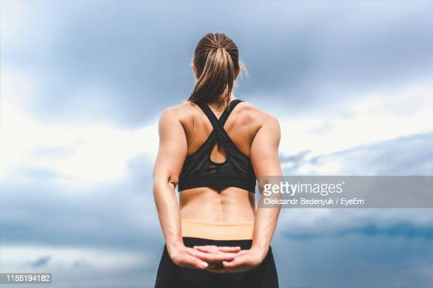 rear view of young woman stretching while exercising outdoors - hands behind back stock pictures, royalty-free photos & images