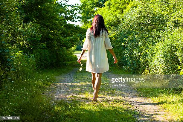 Rear view of young woman strolling barefoot along rural track, Delaware Canal State Park, New Hope, Pennsylvania, USA