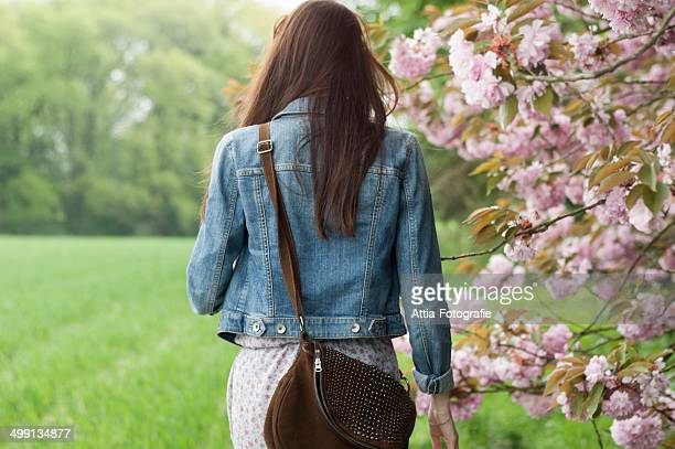 Rear view of young woman strolling in field