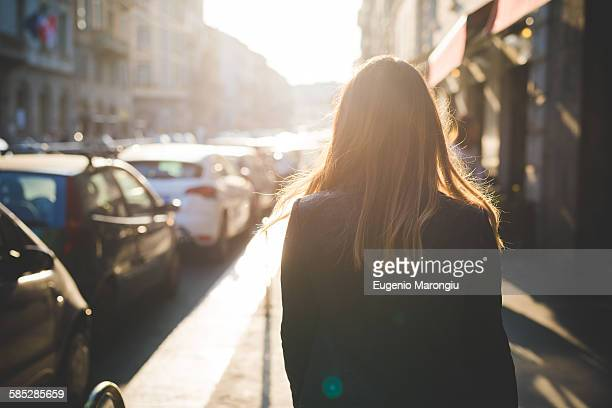 Rear view of young woman strolling on city street