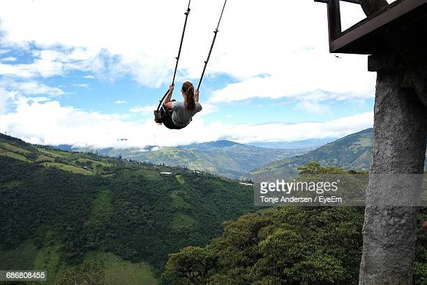 Rear View Of Young Woman Swinging Above Green Mountains
