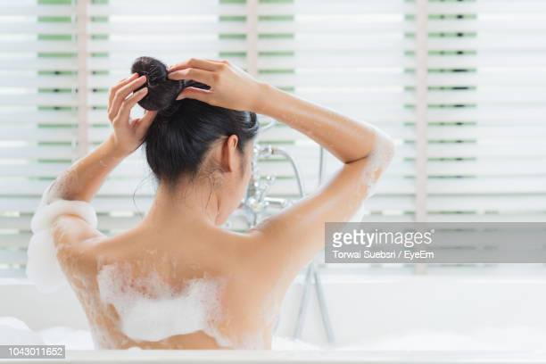 rear view of young woman tying hair while taking bath in bathtub - torwai stock pictures, royalty-free photos & images