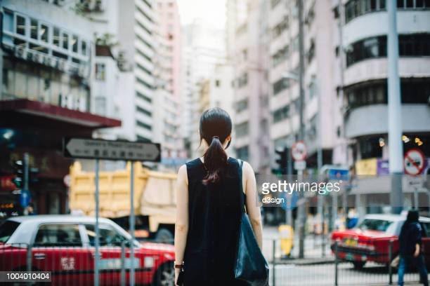 rear view of young woman visiting and exploring city, looking over to busy cityscape - central stock pictures, royalty-free photos & images