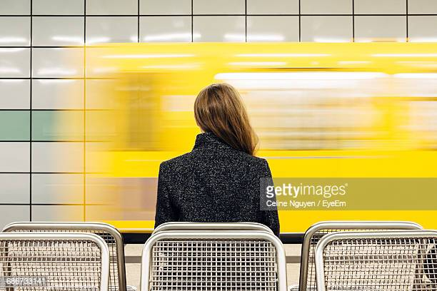 rear view of young woman waiting for subway - underground stock photos and pictures