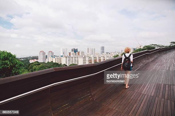 rear view of young woman walking at southern ridges - bortes stock-fotos und bilder