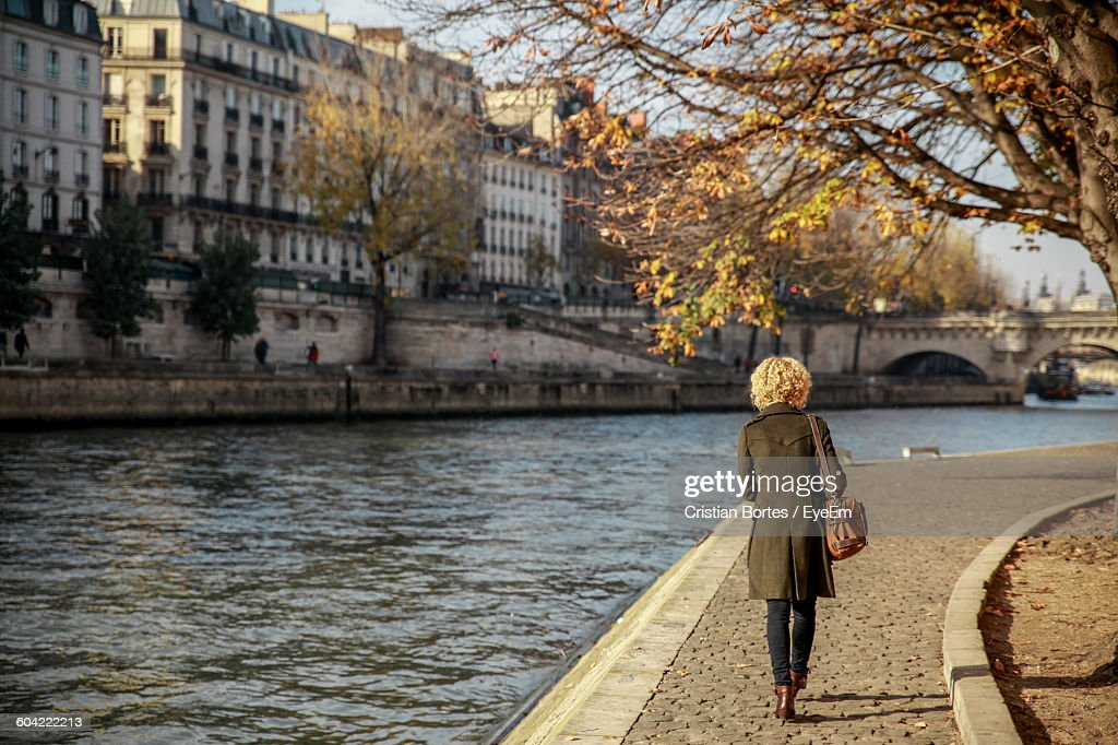 Rear View Of Young Woman Walking By Seine River : Stock Photo