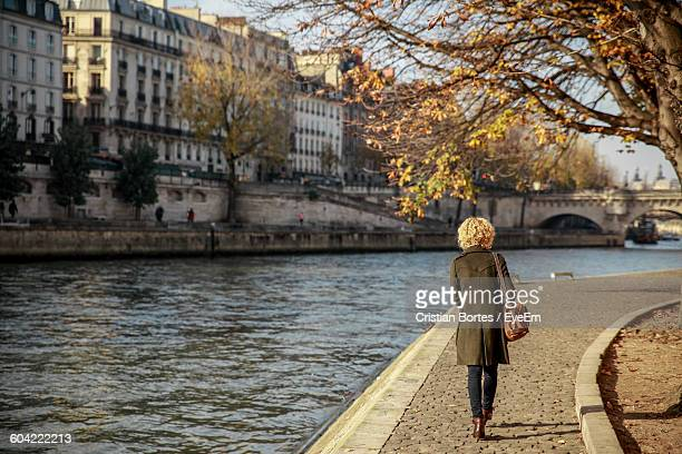 rear view of young woman walking by seine river - riverbank - fotografias e filmes do acervo