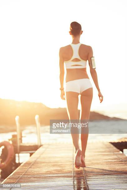 Rear view of young woman walking on a wooden pier