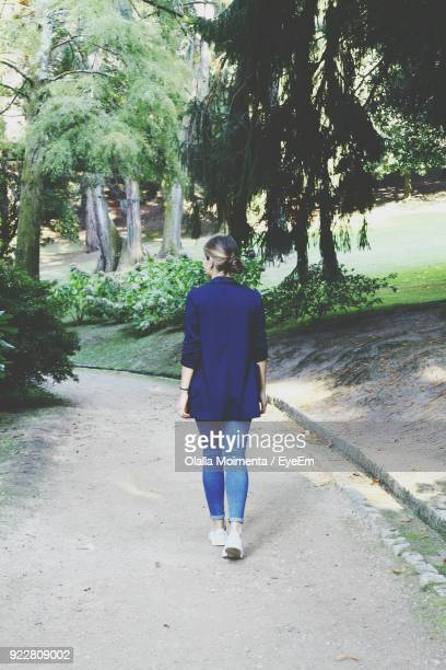 Rear View Of Young Woman Walking On Footpath