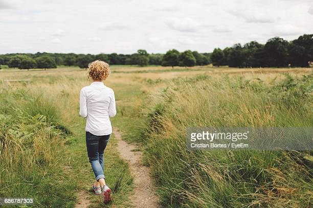 rear view of young woman walking on grassy field - bortes stock pictures, royalty-free photos & images
