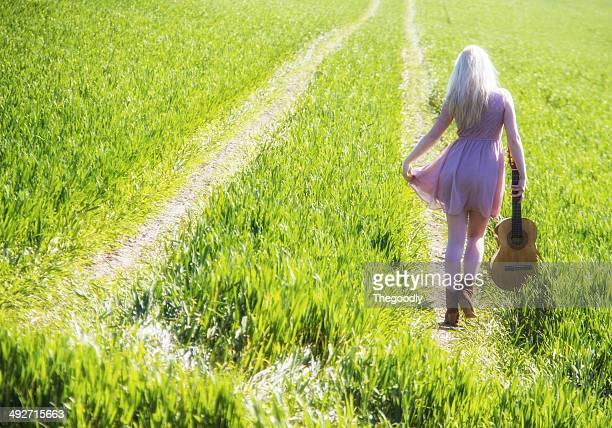 Rear view of young woman walking on green field with guitar