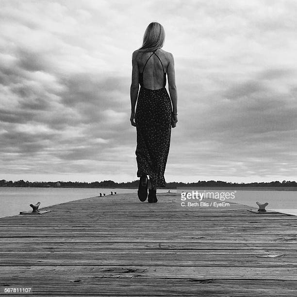 rear view of young woman walking on jetty against sky - long dress stock pictures, royalty-free photos & images