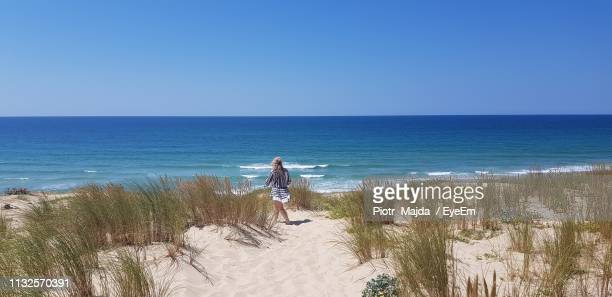 rear view of young woman walking on sand at beach against clear blue sky during sunny day - cap ferret photos et images de collection