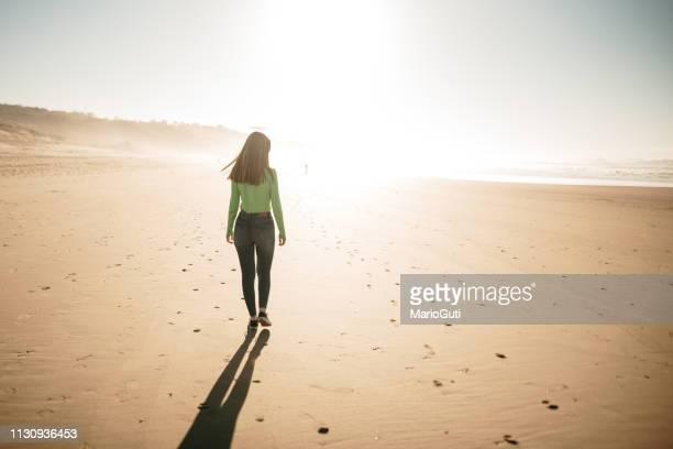 vista trasera de la mujer joven caminando en la playa al atardecer - espalda chica morena playa fotografías e imágenes de stock