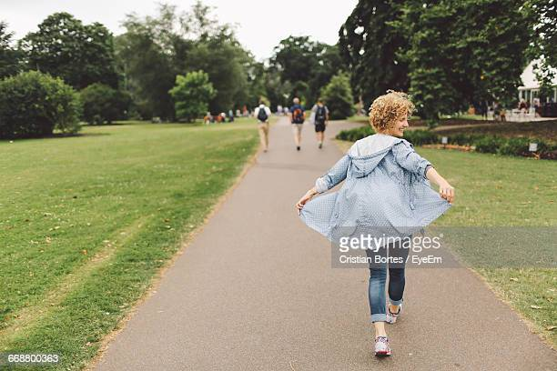 rear view of young woman walking on walkway at park - bortes foto e immagini stock