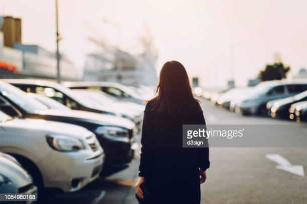 rear view of young woman walking through outdoor car park in city looking for her car - parking lot stock pictures, royalty-free photos & images