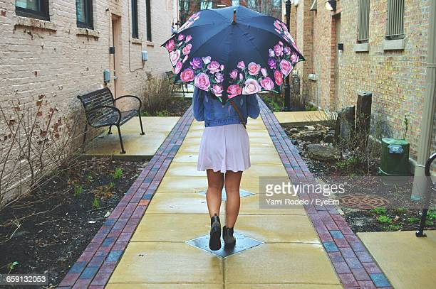 Rear View Of Young Woman Walking Under Umbrella On Footpath Amidst Houses
