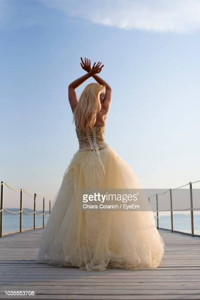 rear view of young woman wearing evening gown standing on pier against sky - ロングドレス ストックフォトと画像