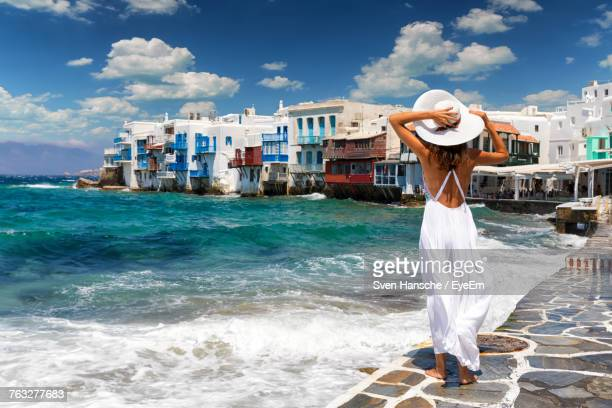 rear view of young woman wearing hat standing at beach against sky during sunny day - ver a hora stockfoto's en -beelden