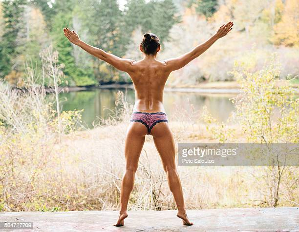 rear view of young woman wearing knickers in front of rural lake - knickers stock-fotos und bilder