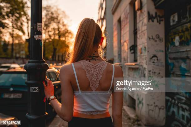 Rear View Of Young Woman While Standing On Sidewalk During Sunset