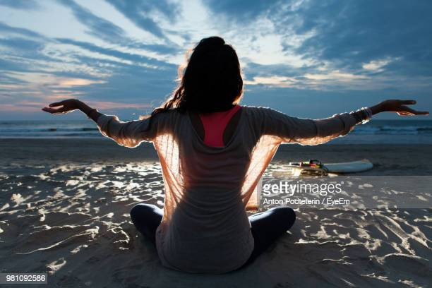 rear view of young woman with arms outstretched sitting at beach against cloudy sky - goa stock pictures, royalty-free photos & images
